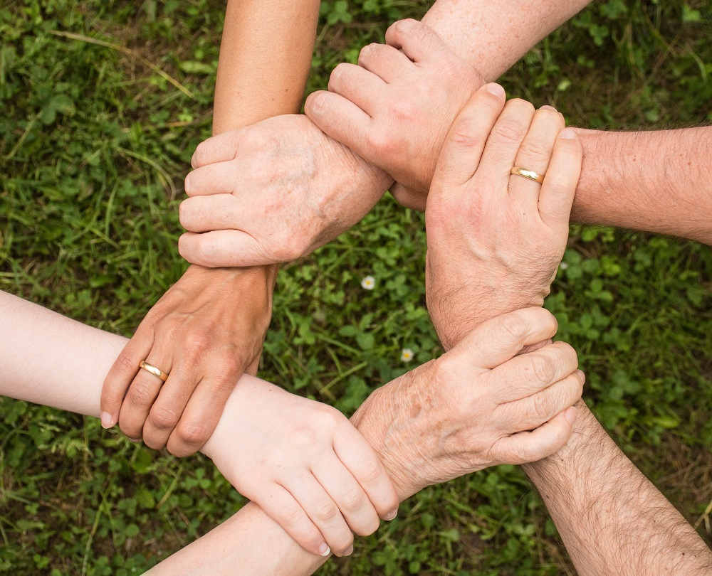Six hands clasped together, representing a family working together on estate planning.
